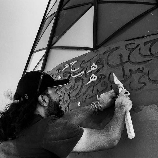 שריף סרחאן במהלך עבודת הקליגרפיה על המגדלור. (צילום באדיבות אתר ערב 48)