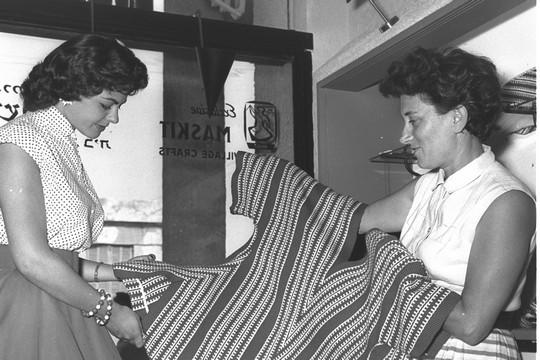 """רות דיין מציגה רקמה תימנית למלכת היופי של ישראל, שרה טל, בחנות של """"משכית""""בתל אביב, 1956 (הנס חיים פין, אוסף התצלומים הלאומי)"""