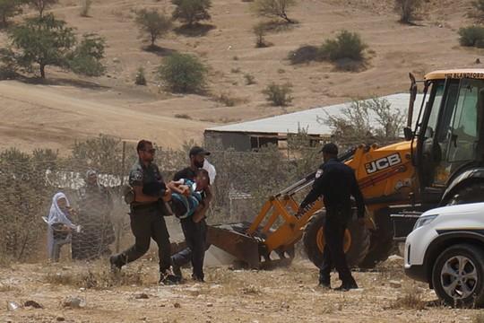 המשטרה עוצרת את אחד מצעירי הכפר אום אל חיראן שמחו על תחילת הקמתה של גדר סמוך לבתי הכפר. 31 ביולי 2016. (התמונה באדיבות פורום דו קיום בנגב)