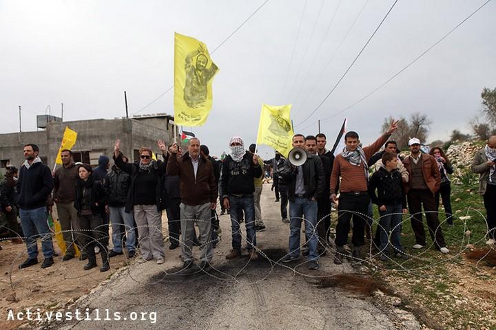 מפגינים ניצבים מאחורי גדר תיל שנפרסה בכביש על ידי הצבא בזמן הפגנה נגד הכיבוש וההתנחלויות בכפר קדום 30 בדצמבר 2011 (אקטיבסטילס)
