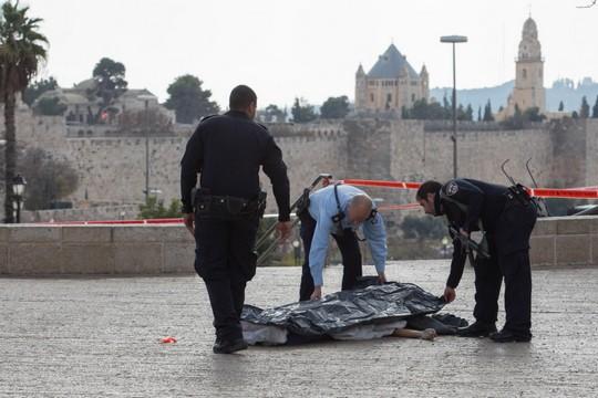 """כוחות הבטחון מכסים את גופתו של פלסטיני שניסה לדקור שוטר בכיכר צה""""ל בירושלים ונורה למוות. (צילום: פלאש90)"""