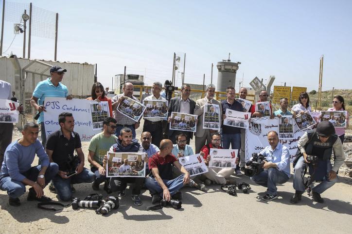 עיתונאים פלסטינים מפגינים בסולידריות עם העיתונאי עומר נזאל מחוץ לכלא עופר לאחר שנעצר במעבר אלנבי. 26 באפריל 2016. (פלאש90)