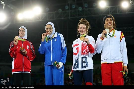"""מדליסטיות ערביות על הפודיום. זוכות הארד הדאיה מלאכ ממצרים ולצדה קימיה עליזאדה – האשה האיראנית הראשונה שזוכה במדליה אולימפית. טורניר טאקוונדו עד 57 ק""""ג, אולימפיאדת ריו 2016. (צילום: מוחמד חסנזאדה, ויקימדיה)"""