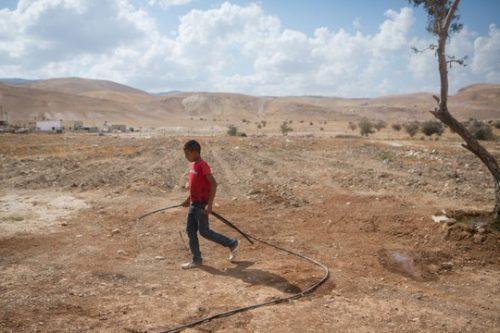 ילד עם צינור מים באזור פסאיל, בקעת הירדן (מרים אלסטר / פלאש90)