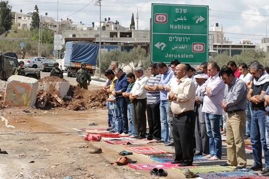 תושבי ביתא מקיימים תפילת מחאה מול מחסום העפר שהקימה ישראל בכניסה לכפר שלהם שחוסמת את הגישה גם לכביש 60. ישראל הטילה את הסגר לפני חמישה ימים. 23 בספטמבר 2016 (אחמד אל-באז / אקטיבסטילס)