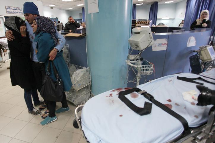 בני משפחתו של סמיר עוואד ליד מיטה בבית החולים אליו נלקח (עיסאם רימאווי / פלאש90)