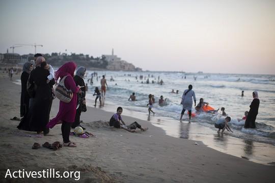נשים צופות בקרוביהן שוחים בים מצפון ליפו. עיד אל אדחא. 14 בספטמבר 2016 (אורן זיו/אקטיבסטילס).