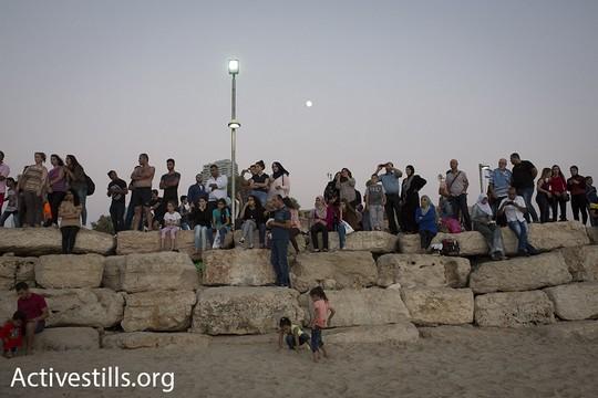 משפחות פלסטיניות צופות בשקיעה בחוף הים מצפון ליפו. בעוד רגע יפקע תוקף האישורים שחילקה ישראל והם ישובו לבתיהם בגדה המערבית. 14 בספטמבר 2016. (אורן זיו/אקטיבסטילס).