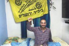 """דוד מזרחי בביתו עם דגל בית""""ר מעל המיטה (מיכאל סולסברי-כורך)"""