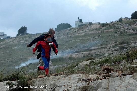 המורה להיסטוריה וילד ספיידרמן בורחים מגז מדמיע שיורים חיילים. שוברט בהפגנה בני סאלח.(צילום: חיים שוורצנברג)