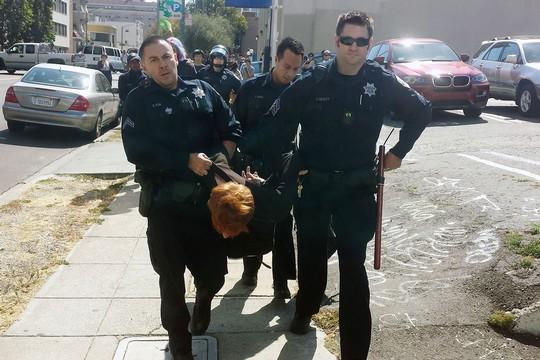שוטרים עוצרין מפגין במהלך הפגנת תמיכה בשביתת האסירים ובקריאה להפסקת העבדות בבתי הכלא באוקלנד (צילום: בראדלי אלן)