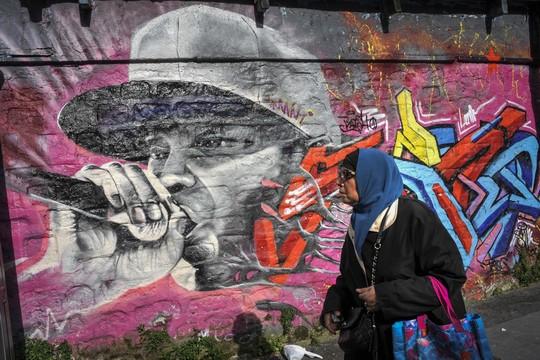 """החיים על הסט של """"אללה אסלאם"""", לא מה שחשבתם. אישה מוסלמית על רקע גרפיטי בפריז. (צילום: סרג' אטל/פלאש90)"""