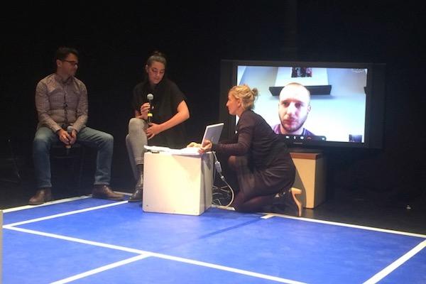"""משמאל: הבמאי מיראז בזר והאוצרת מרי אל-קלקילי מדברים עם התסריטאי אמסעיל חלידי (על המסך) על ההצגה """"טניס בשכם"""" (אנה-אסתר יונס)"""