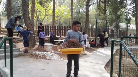 ילדים מנקים את אזור בית הספר אחרי השריפה. נווה שלום - וואחת אל-סלאם (Lindsay Stanek)