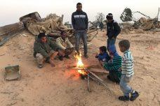 תושבי הכפר ביר הדאג' מתחממים ליד מדורה אחרי הריסות בתים בכפר (רמי יונס)