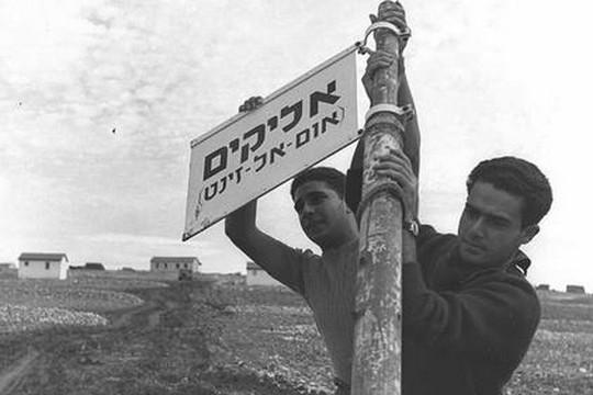 """הצבת השלט """"אליקים"""" במקום בו היה הכפר הערבי אום א-זינאת, 1950 (טדי ברונר/לע""""מ)"""