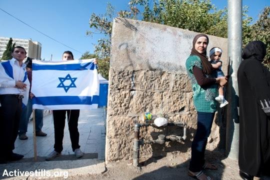 אישה פלסטינית העומדת מחוץ לבית עליו השתלטו מתנחלים בשכונת שייח׳ ג׳ראח בירושלים (ריאן רודריק ביילר/אקטיבסטילס)