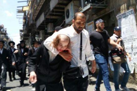 """שוטר סמוי גורר ילד שנפצע ממכות השוטרים ברחובות """"מאה שערים"""" (צילום: """"מחאת החרדים הקיצוניים"""")"""