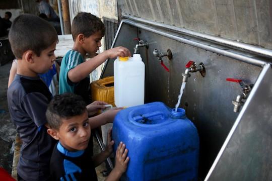 ילדים פלסטינים ממלאים מיכלים במים במחנה הפליטים רפיח בדרום רצועת עזה. יוני 2017 (עבד רחים חטיב/פלאש90)