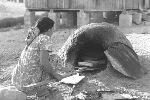 מהגרת מכינה עוגות בתנור אבן ישן בירוחם בנגב (צילום: לשכת העיתונות הממשלתית)