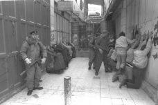 """שוטרי מג""""ב עוצרים פלסטינים בחברון. ינואר 1990. תמונת ארכיון מהאינתיפאדה הראשונה (צילום: נתן אלפרט/ לעמ)"""