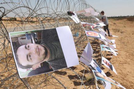 פעילים תולים תמונות של 119 מהרוגי הירי הישראלי על צעדות השיבה בגבול עזה. 26 ביוני 2018. (אורן זיו / אקטיבסטילס)