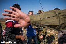 חייל מנסה לחסום צילום של פלסטינים (אילוסטרציה: אן פאק / אקטיבסטילס)