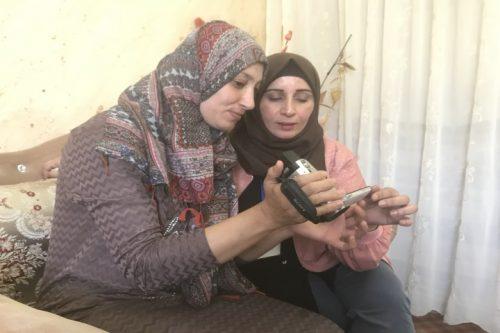 """""""אם לא הייתי מצלמת? הייתי מוצאת דרך לצלם. זו השליחות שלי"""". מנאל אל-ג'עברי ואריג' אל-ג'עברי צופות בסלון ביתהב של אריג' בוידאו שהיא צילמה (רמי יונס)"""