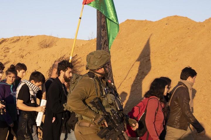 """""""עמנואל ברוש"""" (מזוקן, מאחורי החייל) במחאת ההזדהות עם תושבי עזה ליד הגדר. בדף הפייסבוק שלו עודד את המפגינים (צילום: אורן זיו / אקטיבסטילס)"""