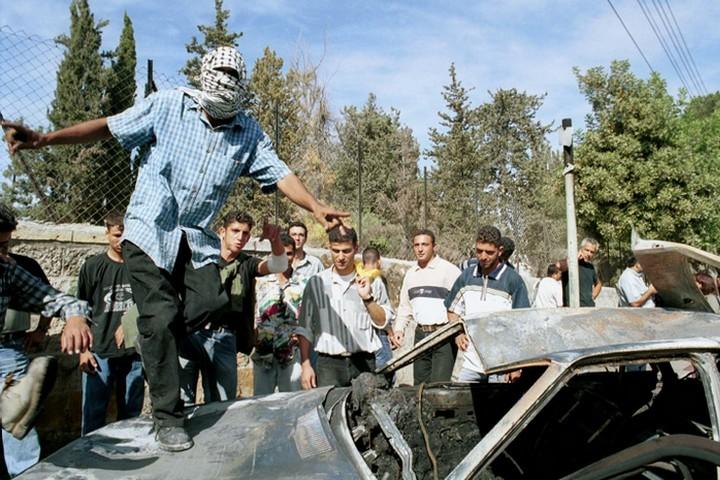 ואדים נורז'יץ ויוסי אברהמי נרצחו אחרי שמסרו את נשקם. זה פשע לפי החוק הבינלאומי. פלסטינים ליד המכונית השרופה של שני חיילי המילואים הישראלים (צילום: פלאש 90)