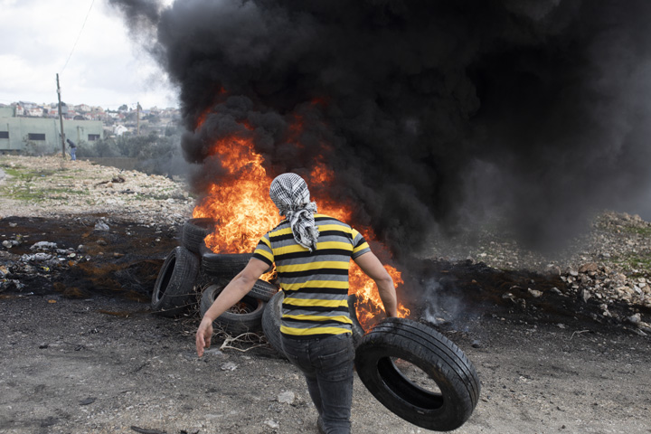 צעיר פלסטיני משליך צמיג לאש, במהלך ההפגנה השבועית נגד הכיבוש וההתנחלויות בכפר קדום שבגדה המערבית (צילום: אורן זיו)