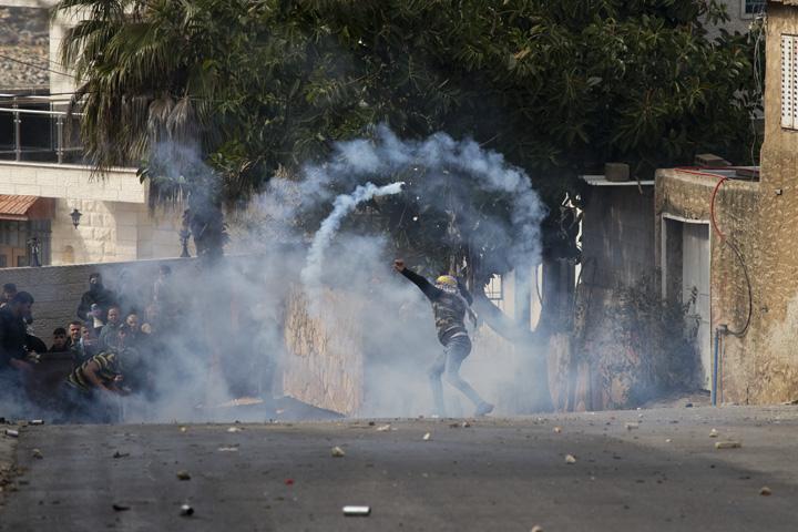 צעיר פלסטיני זורק בחזרה גז מדמיע לעבר חיילים, במהלך ההפגנה השבועית נגד הכיבוש וההתנחלויות בכפר קדום שבגדה המערבית (צילום: אורן זיו)