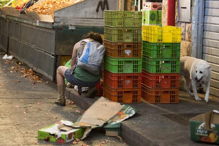 אישה מחפשת ירקות בשוק מחנה יהודה (צילום: נעם רבקין פנטון / פלאש90)