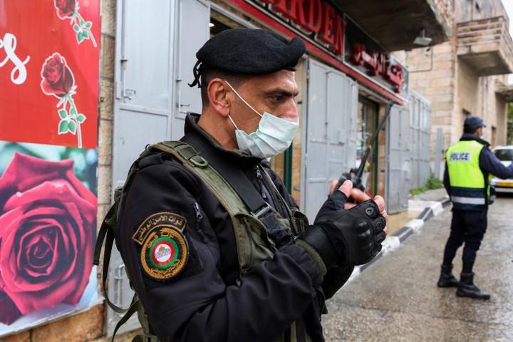 מתנדבים צעירים מחלקים אוכל שמגיע מערים פלסטיניות אחרות. שוטר פלסטיני באזור שהתגלתה בו קורונה בבית לחם (צילום: ויסאם השלמון / פלאש 90)