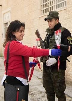 האמון בכוחות הביטחון חזר. כיפאח מנסרה מחלקת פרחים לשוטרים. (צילום: נור מנאסרה)