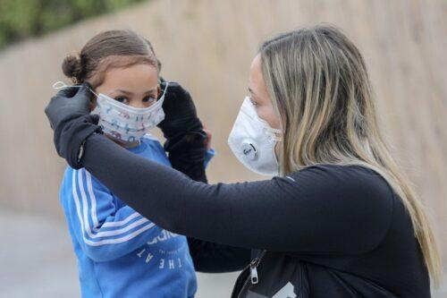מפוטרות ראשונות ונאלצות להישאר בבית עם הילדים. אשה מלבישה לבתה מסכה. למצולמות אין קשר לכתבה (צילום: יוסי אלוני / פלאש 90)