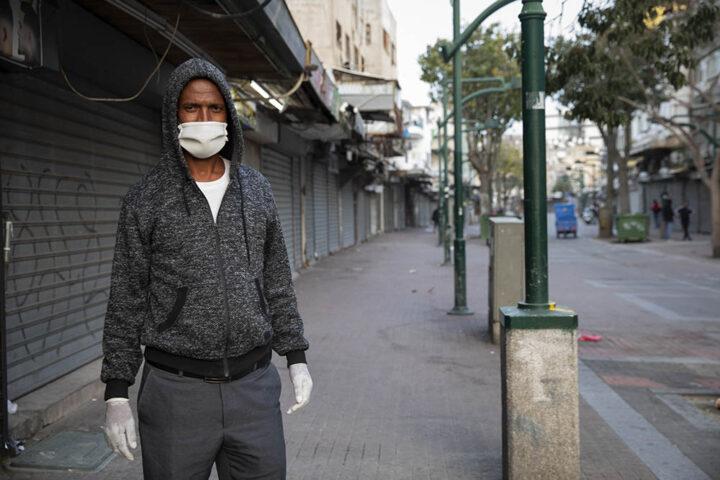 מבקש מקלט על רקע מדרחוב נווה שאנן הריק בדרום תל אביב, 31 במרץ 2020 (צילום: אורן זיו)