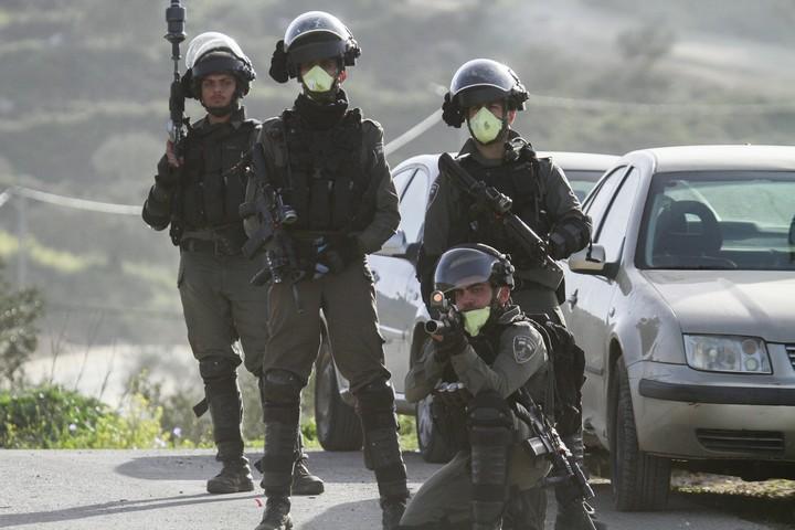 שוטרים לובשים מסכות נגד הקורונה במהלך התנגשויות עם מפגינים פלסטינים בג'בל אל ערמה, ב-11 במרץ 2020 (צילום: נאסר אישתאיה / פלאש 90)