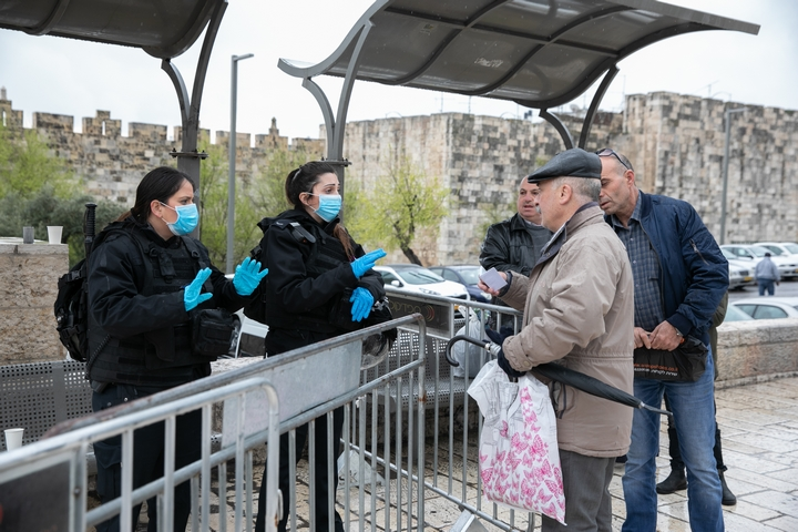 שוטרים ישראלים חבושים מסיכות נגד קורונה בודקים תעודות זהות בכניסה לעיר העתיקה בירושלים (צילום: אוליבייה פיטוסי / פלאש90)