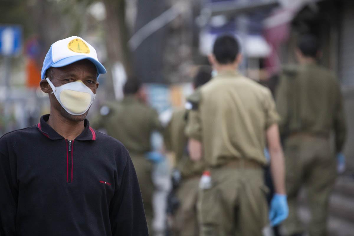 מבקש מקלט בשכונת נווה שאנן בדרום תל אביב, ברקע סיור של חיילים ושוטרים, 31 במרץ 2020 (צילום: אורן זיו)