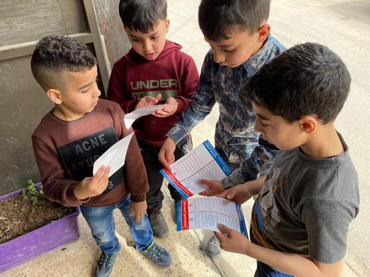 הכי קשורים לסבא וסבתא. ילדים במחנה פליטים שועפאט עם עלוני הסברה על הקורונה (צילום: כאמל ג'עברי)