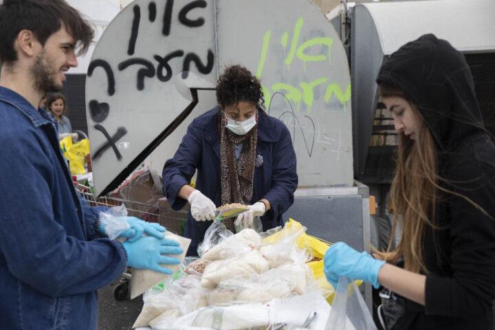 מתנדבים של עמותת אליפלט מכינים סלי מזון למשפחות של מבקשי מקלט, 1 באפריל 2020 (צילום: אורן זיו)