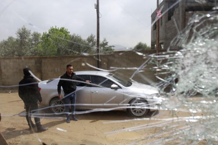 פלסטינים ליד מכוניות שניזוקו מאבנים שהשליכו מתנחלים, ביישוב חווארה שנמצא דרומית לשכם, ב-15 במרץ 2020 (צילום: נאסר אישתאיה / פלאש90)