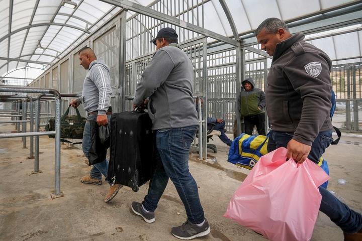 פועלים פלסטינים מחברון מגיעים מצוידים במיטלטליהם כדי לעבור לישראל במחסום טרקומיא, ב-18 במרץ 2020 (צילום: ויסאם השלמון / פלאש90)
