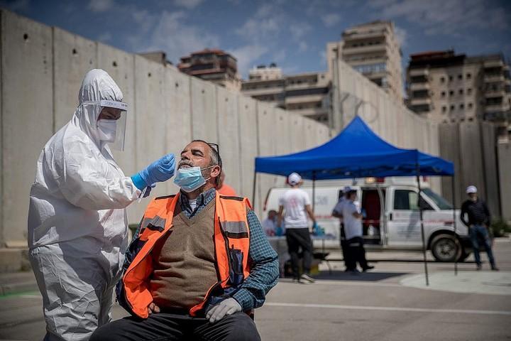 """אנשי מד""""א מבצעים בדיקות קורונה בדרייב-אין ליד מחנה הפליטים שועפאט, ב-16 באפריל 2020 (צילום: יונתן זינדל / פלאש90)"""