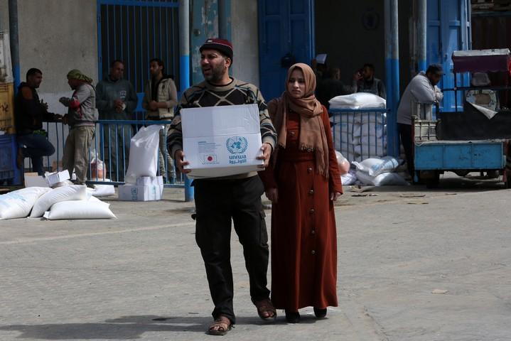 """פלסטינים מקבלים חבילות מזון במרכז של אונר""""א בחאן יונס, ב-7 במרץ 2020 (צילום: פאדי פאהד / פלאש90)"""