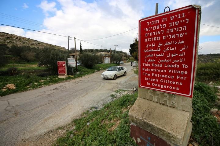 שלטי ענק אדומים מוצבים בכניסות ומזכירים לאזרחים הישראלים כי פלסטינים תחת משטר צבאי חיים בפנים, מה שלעלול להיות מסוכן לחייהם (צילום: אחמד אל-באז / אקטיבסטילס)