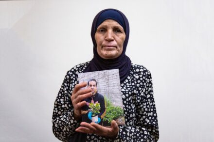 איאד הלך אחריה כמו צל. רנא אלחלאק, אמו של איאד, ששוטרים ירו בן למוות בירושלים, עם תמונת בנה (צילום: אקטיבסטילס)