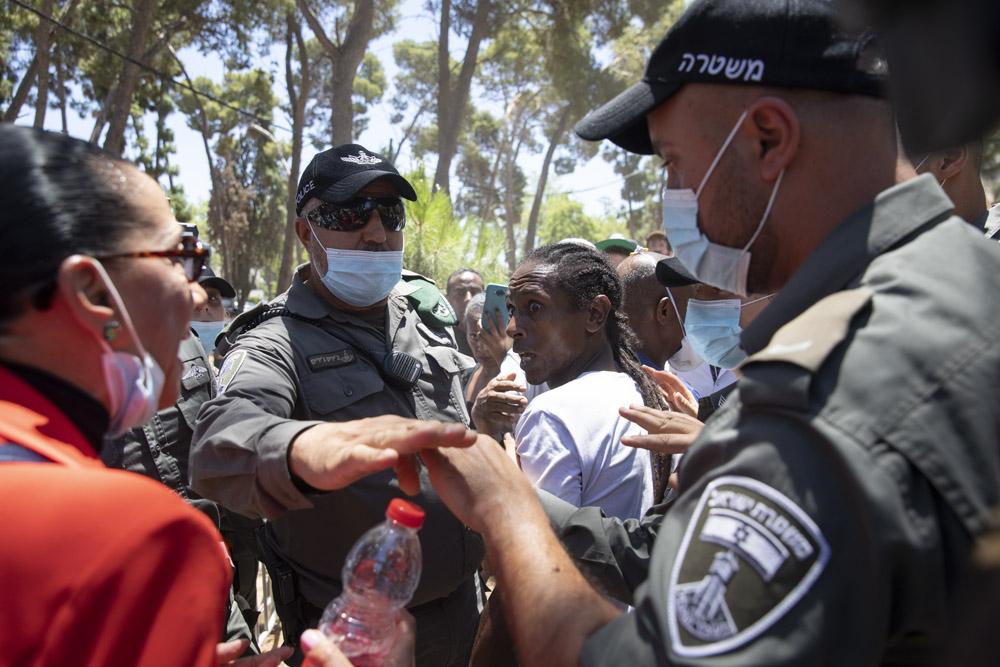 מפגינה שהגיעה לתמוך בשוטר היורה מתווכחת עם מפגין נגד לאימות משטרתית, במהלך סיור של השופט זיאד פאלח בזירת הירי בסלומון טקה בקריית חיים, 23 ביוני 2020 (צילום: אורן זיו)