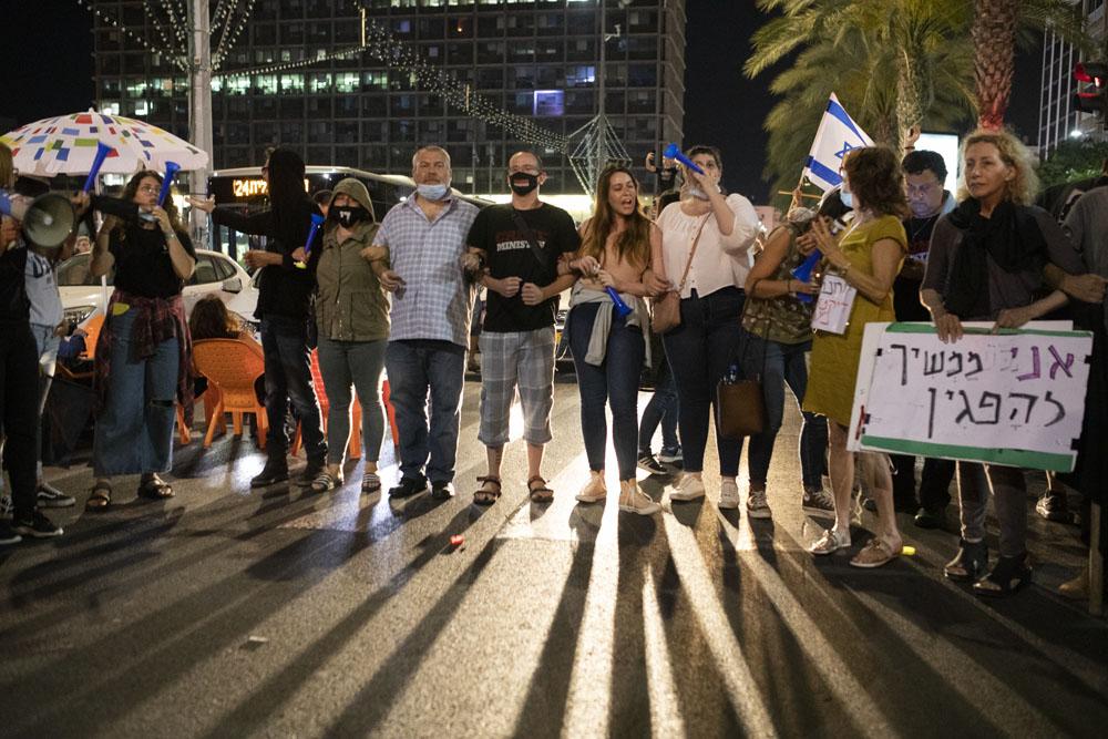 מפגינים חוסמים את רחוב אבן גבירולבמהלך מחאה נגד ״חוק הקורונה״ בתל אביב (צילום אורן זיו)